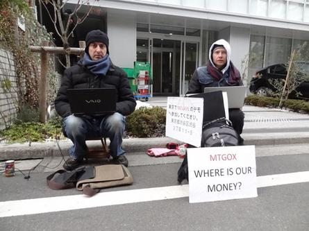 Bitcoin traders protest outside the Tokyo offices of Tibanne, operator of the Mt. Gox bitcoin exchange. Mt. Gox suspended bitcoin withdrawals to outside addresses, citing technical issues.