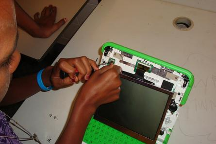 A student at Doomadgee State School replaces the screen on an XO laptop.