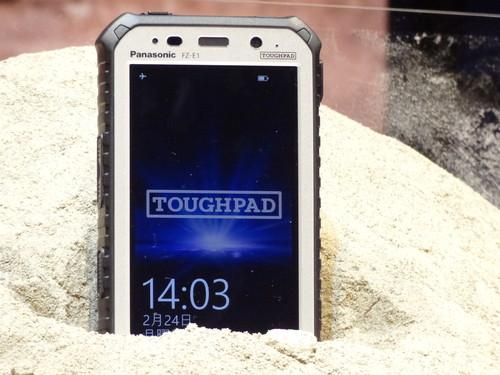 Panasonic's new Toughpad 5-inch rugged tablet with phone functions is seen buried in dirt at its unveiling in Tokyo on Monday.