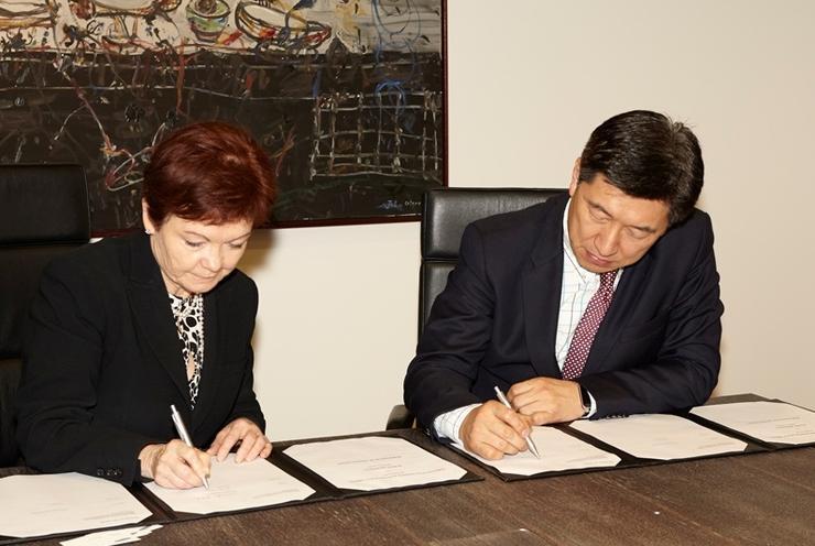 Deakin vice-chancellor, Jane den Hollander, and Samsung Electronics Australia president, Jack Kwon, sign MOU for joint R&D. Credit: Deakin University