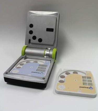 PositiveID has developed a prototype device, the Firefly DX, to conduct quick tests for infectious diseases, including Ebola. The mini-laptop device can be opened to insert testing cartridges inside that include a small hole in the center for taking blood samples.