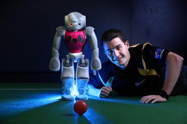 UNSW PhD student Sean Harris with one of the robot soccer players. Photo credit: Grant Turner, Mediakoo.