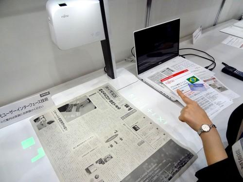 Fujitsu's prototype scanner-projector, dubbed Next Generation User Interface Technology, projects thumbnails of scans of text from a newspaper. Users can outline blocks of text to be scanned with their fingers.