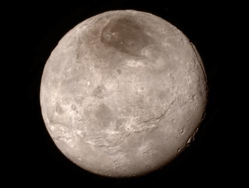 New details of Pluto's largest moon Charon reveal a swath of cliffs and troughs stretching about 600 miles. At upper right, along the moon's curving edge, is a canyon estimated to be four to six miles deep.